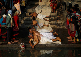 Devotees offer prayers by rolling on the ground during the Swasthani Brata Katha festival in Bhaktapur
