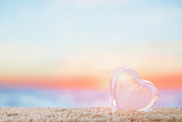 clear heart sea glass  on  beach sand