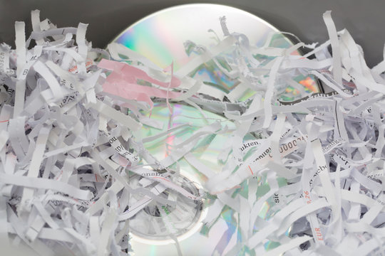 Compact discs and paper scraps after passing sensitive documents through shredding machine