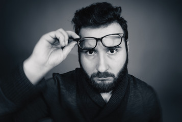 Black and white portrait of a serious man with glasses.