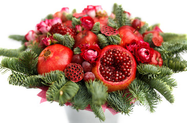 Huge edible fruit bouquet consisting of pomegranates, apples, grapes, rose flowers and fir twigs  on white background. Close-up