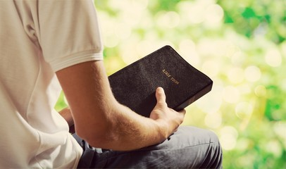 Man reading old Bible book on background