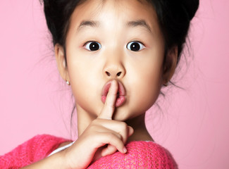Asian kid girl in pink sweater shows shhh quiet sign on pink
