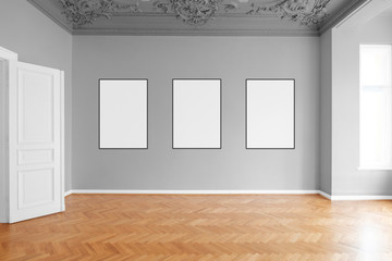 three blank picture frames hanging on wall in empty apartment  room