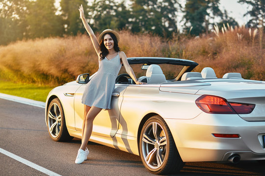 woman with hand up leaning cabrio
