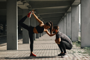 Young sports couple exercising in the urban environment Wall mural