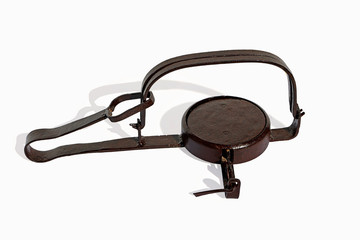 Gin tgin trap; pressed;  iron; vintage; jaws; bow; spring; iron treadle catch; tongue; catch an animal; mechanical device; steel jaws;rabbit trap; capture; small; animals;rap
