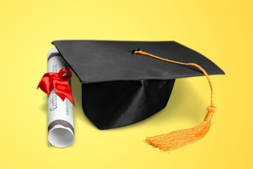 Graduation hat and diploma on yellow background