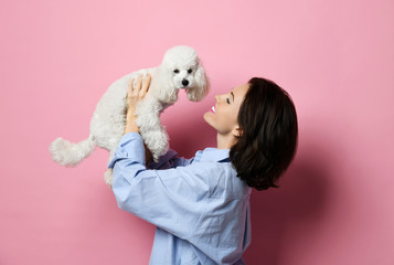 Beautiful woman hugging her lovely white poodle dog puppy on pink