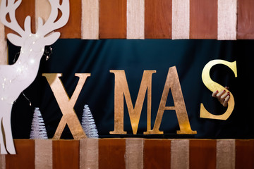 Christmas decoration: The word xmas covered with gold with white reindeer and fir trees. The letter s is being put into place by hands in the background.
