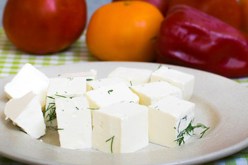 Fresh Greek Feta cheese. Healthy ingredient for salad. Crushed goat cheese with herbs. Pieces of feta cheese on a plate with dill greens