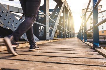 Man walking alone over a bridge at sunset