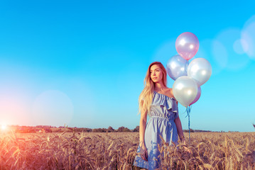 A beautiful girl in blue dress is standing in a field in her hands holding balloons. A party in a wheat field with balls in hand.
