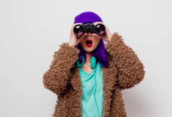 Beautiful young girl with purple hair in jacket looking in to binocular on white background.