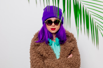 Beautiful young girl with purple hair in jacket with palm leaf on white background.