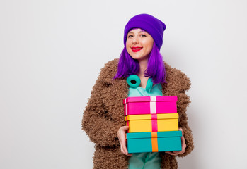 Beautiful young girl with purple hair in jacket with holiday gift boxes on white background.
