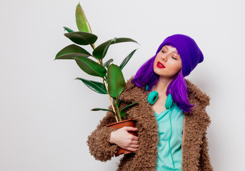 Beautiful young girl with purple hair in jacket with plant on white background.