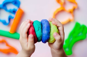 Child hands playing with colorful clay. Homemade plastiline