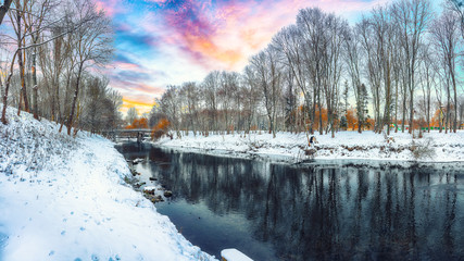 Winter landscape by a river in the sunset.