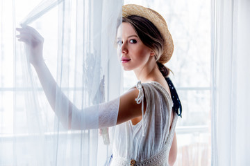 Woman in white dress holding lavender in hands and stay near window. Image in high key style