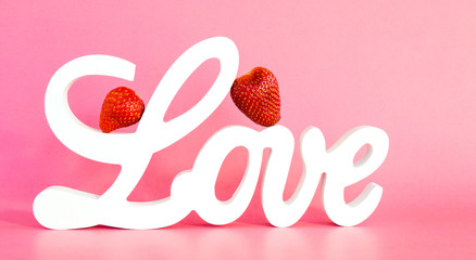 Valentine's Day-white wooden letters spelling the word LOVE with two ripe red strawberries leaning against the L isolated on a pink background