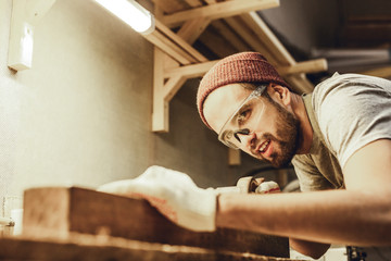 Handsome male in safety goggles smiling and working with piece of wood in joinery Wall mural