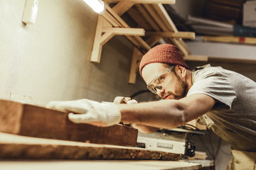 Fototapeta Attractive guy in protection goggles working with lumber plank on workbench in professional joinery obraz
