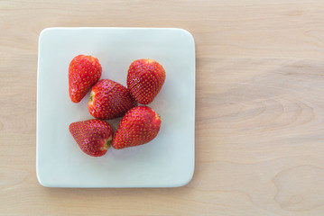 small square plate holding 5 ripe red strawberries on a wooden table with copy space