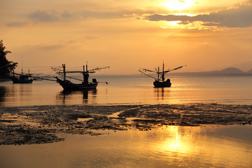 Silhouette fo fishing boats on the sea during sunset at Mae Ramphueng Beach ,Prachuap Khiri Khan province in Thailand.