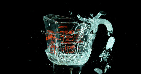 A Glass Measuring Cup Shattering, breaking, exploding into shards isolated on black. Cup still has form handle broke off