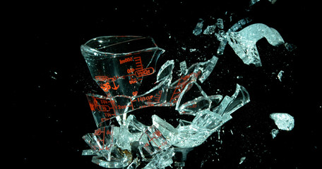A Glass Measuring Cup Shattering, breaking, exploding into shards isolated on black. Cup losing form