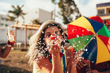 Foto op Aluminium Carnaval Brazilian Carnival. Young woman in costume enjoying the carnival party blowing confetti