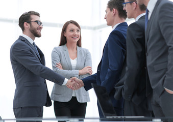 Successful business people shaking hands in an office.