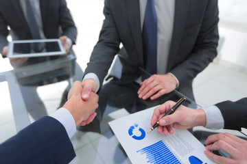 Two businessmen handshaking, congratulating on promotion. Close