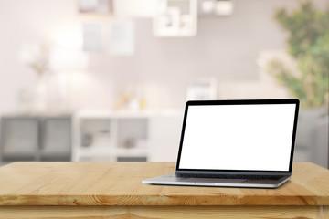 Mockup blank screen laptop on wood table desk in living room background