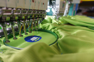 Embroidery machine needle in Textile Industry at Garment Manufacturers, Embroidery T-shirt in progress, Needle with thread (selective focus and soft focus)
