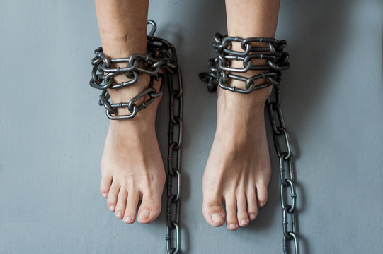 Female legs in chains. Slavery and dependence.