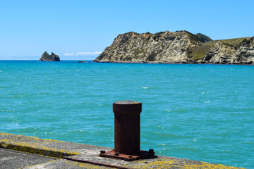 Rusty bollard post a t the end of the wharf in Tolaga Bay, New Zealand.
