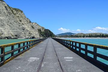 Long shot of the pier under a sunny sky in Tolaga Bay, New Zealand.