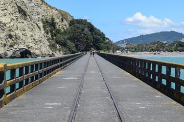 Romantic couple walking along the pier at Tolaga Bay, New Zealand.