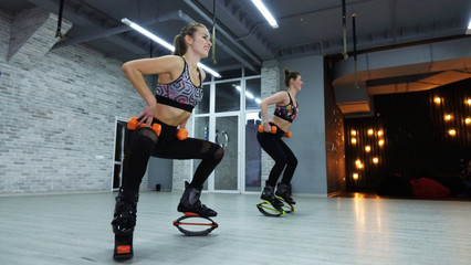 Sports girls with orange dumbbells. The concept of sport and recreation
