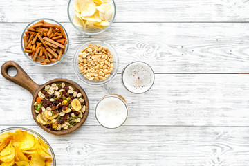 Snacks and beer. Chips, nuts, rusks near beer on white wooden background top view copy space