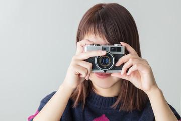 カメラを構える若い女性白背景