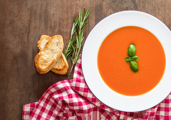 Vegetarian autumn Tomato soup with bread on wooden table, flat lay. Copy space