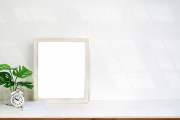 Mock up white wooden frame with blank page and houseplant on white table and white background