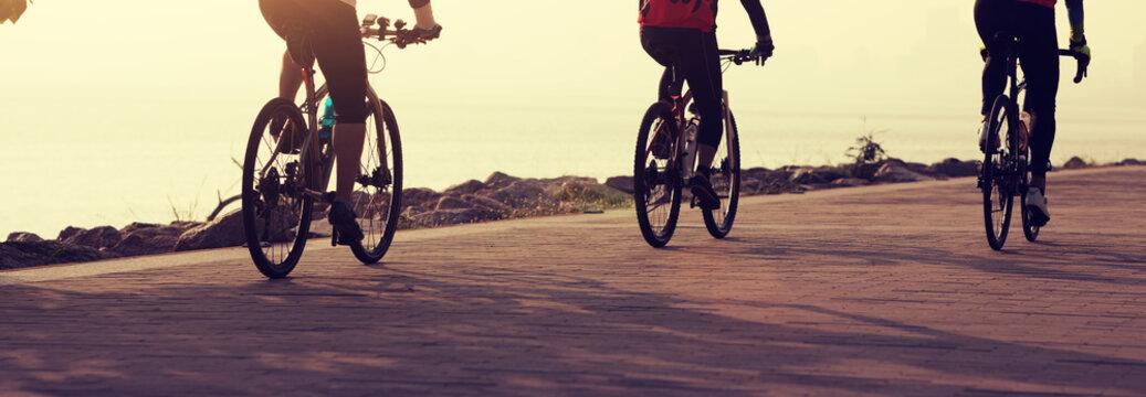 cyclists riding mountain bike on seaside
