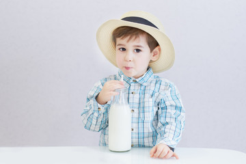 cute happy boy with dark eyes drinks milk from a bottle. checked shirt and hat