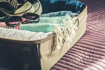 Open suitcase with female clothes for travel. Packing things.