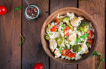 Delicious chicken, broccoli, green peas, tomato stir fry with rice. Asian cuisine. Healthy food. Top view