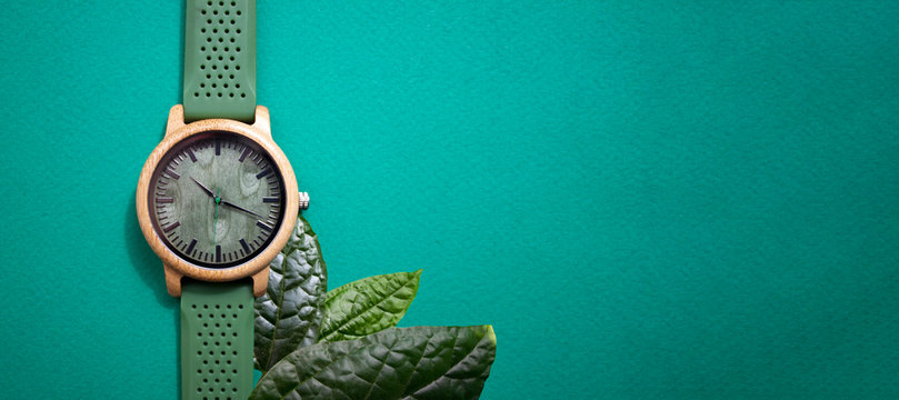 Wooden wristwatch on a green background. Business time concept.